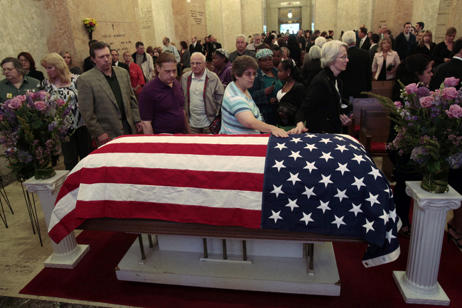 "Mourners file past the flag-draped casket of assisted suicide advocate Jack Kevorkian following a public memorial at White Chapel cemetery in Troy, Michigan June 10, 2011. Kevorkian, known as ""Dr. Death"" for helping more than 100 people end their lives. REUTERS/Rebecca Cook"