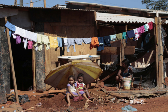 Two children sit in front of their home in the Santa Luzia slum, in Brasilia May 30, 2014. REUTERS/Joedson Alves
