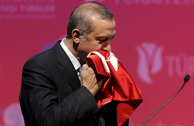 Ankara, TurkeyTurkey's President Tayyip Erdogan kisses a handmade Turkish flag, given to him as a gift from Ugandan university student Cemil (not pictured), during a graduation ceremony in Ankara, Turkey, June 11, 2015. REUTERS/Umit Bektas