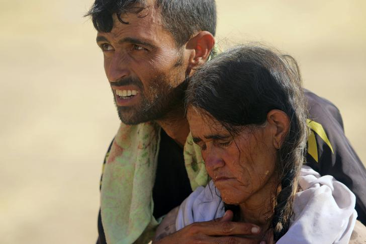A displaced man and a woman from the minority Yazidi sect, fleeing violence from forces loyal to the Islamic State in Sinjar town, walk towards the Syrian border, on the outskirts of Sinjar mountain, near the Syrian border town of Elierbeh of Al-Hasakah Governorate August 11, 2014. REUTERS/Rodi Said