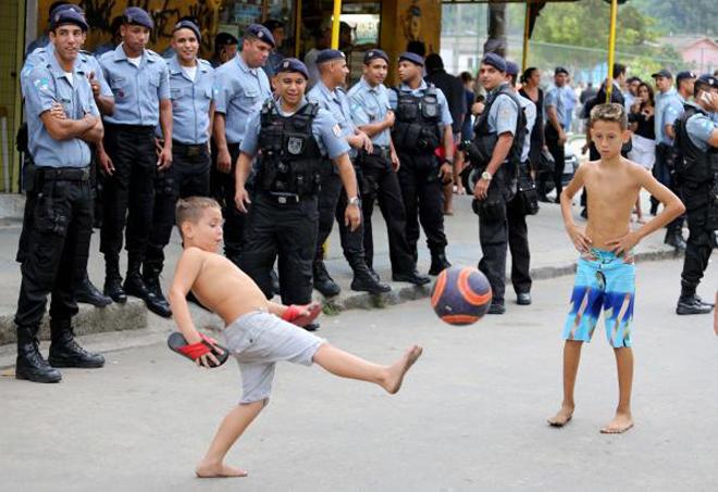 Bambini giocano a calcio per strada sotto lo sguardo degli uomini delle UPP. Photo credits UPP