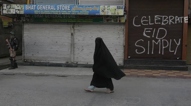 Una donna cammina di fronte alle serrande dei negozi chiusi. I leader separatisti hanno esortato la popolazione a celebrare Eid con semplicità, nel rispetto della tragica situazione in Kashmir. Credit: AP