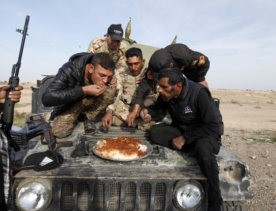 Members of Iraqi security forces and Shiite fighters eat on their vehicle on the outskirts of Baiji, north of Baghdad December 8, 2014. REUTERS/Ahmed Saad