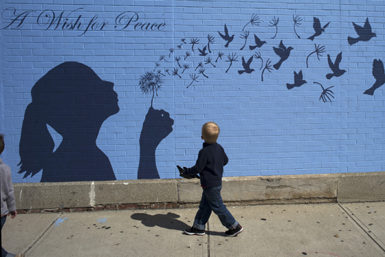 A boy looks up at a mural reading