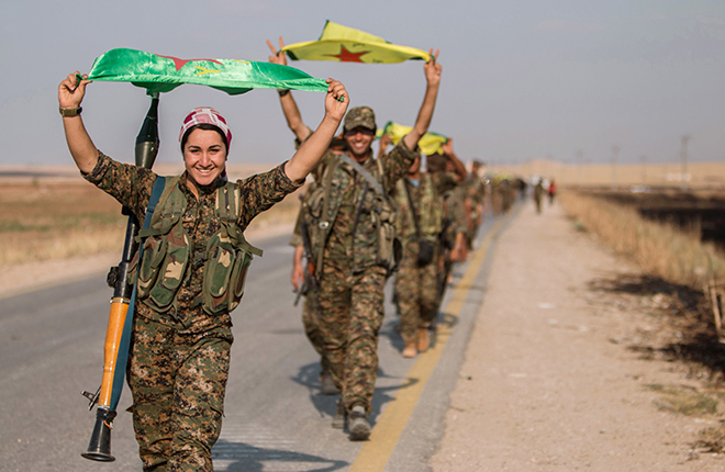 Raqqa, SyriaKurdish fighters gesture while carrying their parties' flags in Tel Abyad of Raqqa governorate after they said they took control of the area June 15, 2015. Syrian Kurdish-led forces said they had captured a town at the Turkish border from Islamic State on Monday, driving it away from the frontier in an advance backed by U.S.-led air strikes that has thrust deep into the jihadists' Syria stronghold. The capture of Tel Abyad by the Kurdish YPG and smaller Syrian rebel groups means the Syrian Kurds effectively control some 400 km (250 miles) of the Syrian-Turkish border that has been a conduit for foreign fighters joining Islamic State. Picture taken June 15, 2015. REUTERS/Rodi Said