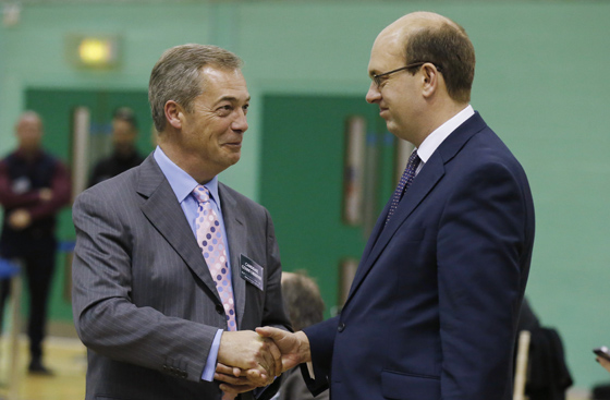 Nigel Farage (L), leader of the United Kingdom Independence Party (UKIP), shakes hands with Mark Reckless, the former Conservative Party member of Parliament for Rochester and Strood, during the by-election ballot count at Medway Park in Gillingham, southeast England, November 21, 2014. REUTERS/Suzanne Plunkett