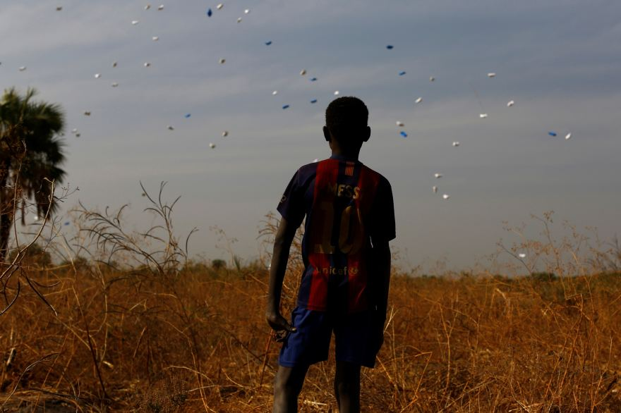 A boy watching the packages containing basic necessities launched by the United Nations, near the village of Rubkuai, in northern South Sudan. Credits Siegfried Modola, Reuters/Contrasto