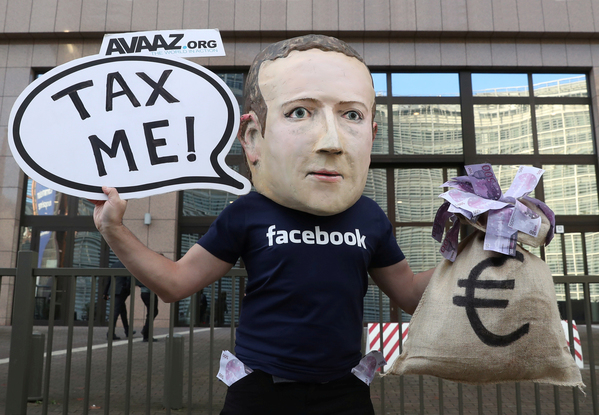 An activist wearing a mask in the likeness of Facebook CEO Mark Zuckerberg at a demonstration held during the meeting between European Union finance ministers in Brussels. REUTERS/YVES HERMAN