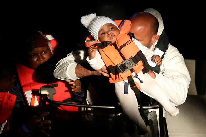 "Officers from ""Fiorillo"" Italian Coast Guard vessel hold a child rescued by ""Save the Children"" NGO crew in the Mediterranean sea off the Libyan coast, June 16, 2017. REUTERS/Stefano Rellandini"
