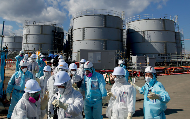 Journalists in protective clothing on a visit to the nuclear power station of Fukushima Daiichi. Although the radiation from the Fukushima disaster doesn't appear to have caused any deaths, the reclamation costs have been crippling and the environmental impact is expected to be severe.