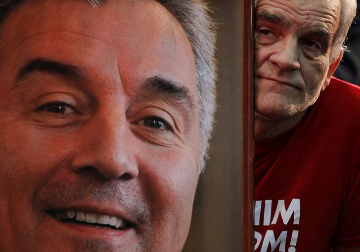 Un sostenitore del Partito democratico dei socialisti sbircia da dietro una foto di Milo Djukanovic. Podgorica, Montenegro. REUTERS / Stevo Vasiljevic