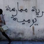 """Una donna tunisina cammina accanto ad un muro con la scritta """"La libertà è una pratica quotidiana"""" a Tunisi. REUTERS / Anis Mili"""
