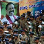 I membri della Task Force speciale dello Sri Lanka e la polizia fanno la guardia accanto a un poster del nuovo primo ministro Mahinda Rajapaksa dopo che una guardia di sicurezza ufficiale del ministro licenziato Arjuna Ranatunga ha sparato e ferito tre persone di fronte alla Ceylon Petroleum Corporation, a Colombo, Sri Lanka 28 ottobre 2018. REUTERS / Dinuka Liyanawatte