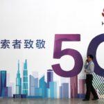 Un uomo parla al telefono accanto al cartellone pubblicitario di Huawei con tecnologia 5G al PT Expo di Pechino, in Cina, 26 settembre 2018. Foto scattata il 26 settembre 2018. REUTERS / Traversa