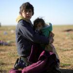 Un giovane ragazzo tiene un bambino vicino al villaggio di Baghouz, provincia di Deir Al Zor, Siria, 1 marzo 2019. REUTERS/Rodi Said