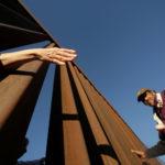 Una persona in piedi sul lato americano del recinto di confine tra il Messico e gli Stati Uniti durante un servizio interreligioso contro il muro del confine del Presidente Donald Trump, a Ciudad Juarez, Messico, 26 febbraio 2019. REUTERS/Jose Luis Gonzalez