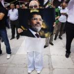 Una donna tiene un poster di Mohamed Morsi durante una dimostrazione filoislamista nel cortile della moschea Fatih a Istanbul, 27 luglio 2013. REUTERS/Murad Sezer