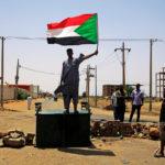Un manifestante sudanese tiene la bandiera nazionale mentre si trova su una barricata lungo una strada, chiedendo che il Consiglio militare di transizione del Paese consegni il potere ai civili, Khartoum, Sudan, 5 giugno 2019. REUTERS/Traversa