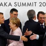 Il Presidente francese Emmanuel Macron stringe la mano al Presidente della Commissione Europea Jean-Claude Juncker, accanto al Primo Ministro spagnolo Pedro Sanchez e alla cancelliera tedesca Angela Merkel, durante una conferenza stampa al vertice del G20 a Osaka, Giappone, 29 giugno 2019. REUTERS/Jorge Silva