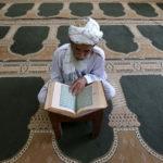 Un uomo afgano mentre legge il Corano. REUTERS/Mohammad Shoib /Contrasto