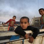 Alcuni bambini stanno sul retro di un camion mentre fuggono dalla città di Ras al Ain, Siria, 9 ottobre 2019. REUTERS/Rodi Said