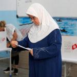 Una donna legge la sua scheda elettorale in un seggio elettorale durante le elezioni parlamentari, a Tunisi, Tunisia, 6 ottobre 2019. REUTERS/Zoubeir Souissi
