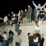Cittadini salgono sul muro di Berlino alla Porta di Brandeburgo per celebrare l'apertura del confine con la Germania dell'Est del 9 novembre 1989. REUTERS/Herbert Knosowski