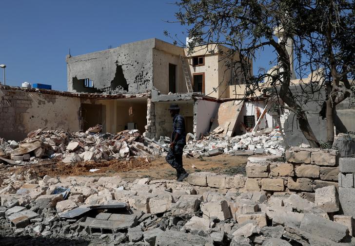 Un membro della sicurezza ispeziona il sito di un attacco aereo notturno che ha colpito un distretto residenziale di Tripoli, Libia, 14 ottobre 2019. REUTERS/Ismail Zitouny