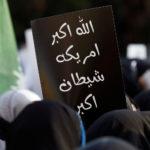"""I musulmani sciiti pakistani portano un cartello con la scritta in urdu """"Allah è grande - L' America è un grande male"""" per protestare contro la morte del generale iraniano Qassem Suleimani, ucciso in un attacco aereo vicino a Baghdad, mentre marciano su una strada che conduce verso il consolato americano a Karachi, Pakistan, 5 gennaio 2020. REUTERS/Akhtar Soomro"""