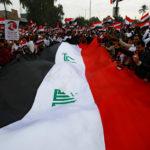 I sostenitori di Moqtada al-Sadr portano un'enorme bandiera irachena in segno di protesta contro la presenza e le presunte violazioni degli Stati Uniti in Iraq, a Baghdad, Iraq, 24 gennaio 2020. REUTERS/Alaa al-Marjani