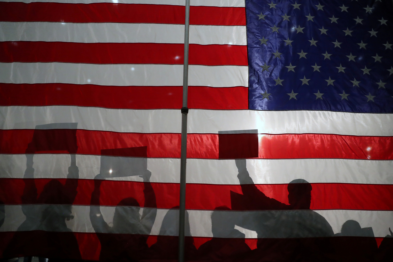 Sagome di partecipanti di fronte alla bandiera americana durante una manifestazione organizzata dal candidato democratico, il senatore americano Bernie Sanders, a Sioux City, Iowa, Usa, 26 gennaio 2020. REUTERS/Ivan Alvarado
