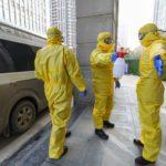 I membri dello staff della sala funebre con tute protettive aiutano un collega con disinfezione dopo aver trasferito un corpo in un ospedale, a seguito allo scoppio del coronavirus a Wuhan, provincia di Hubei, Cina, 30 gennaio 2020. China Daily via REUTERS