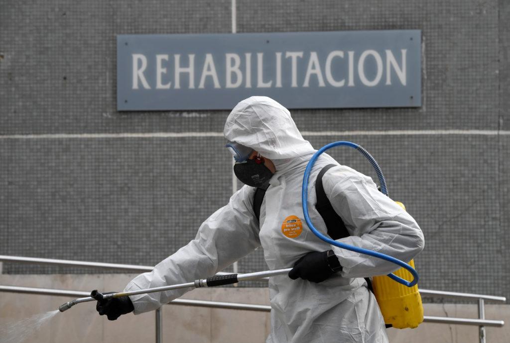 Un membro dell'Unità di emergenza militare (UME) spruzza disinfettante per prevenire la diffusione del coronavirus