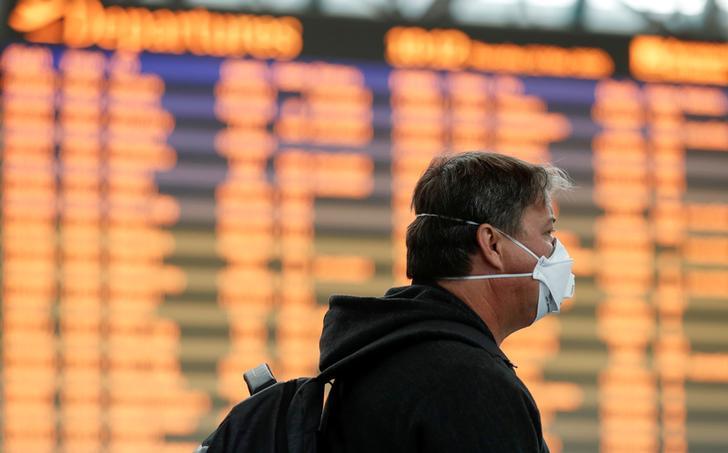 Un uomo indossa una maschera protettiva all'aeroporto di Fiumicino.