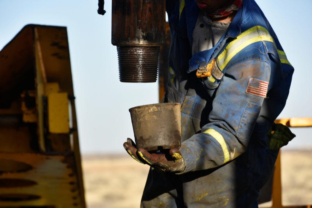 Un operaio petrolifero rimuove un tappo filettato da un pezzo di tubo di trivellazione