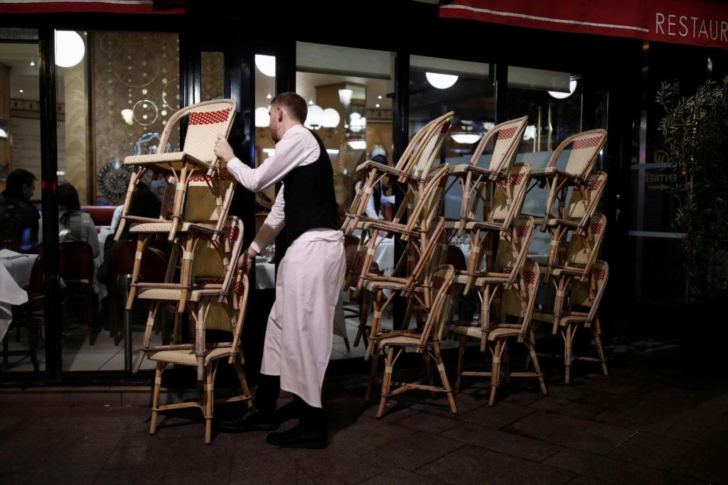 Un cameriere prepara la chiusura del ristorante a Parigi.