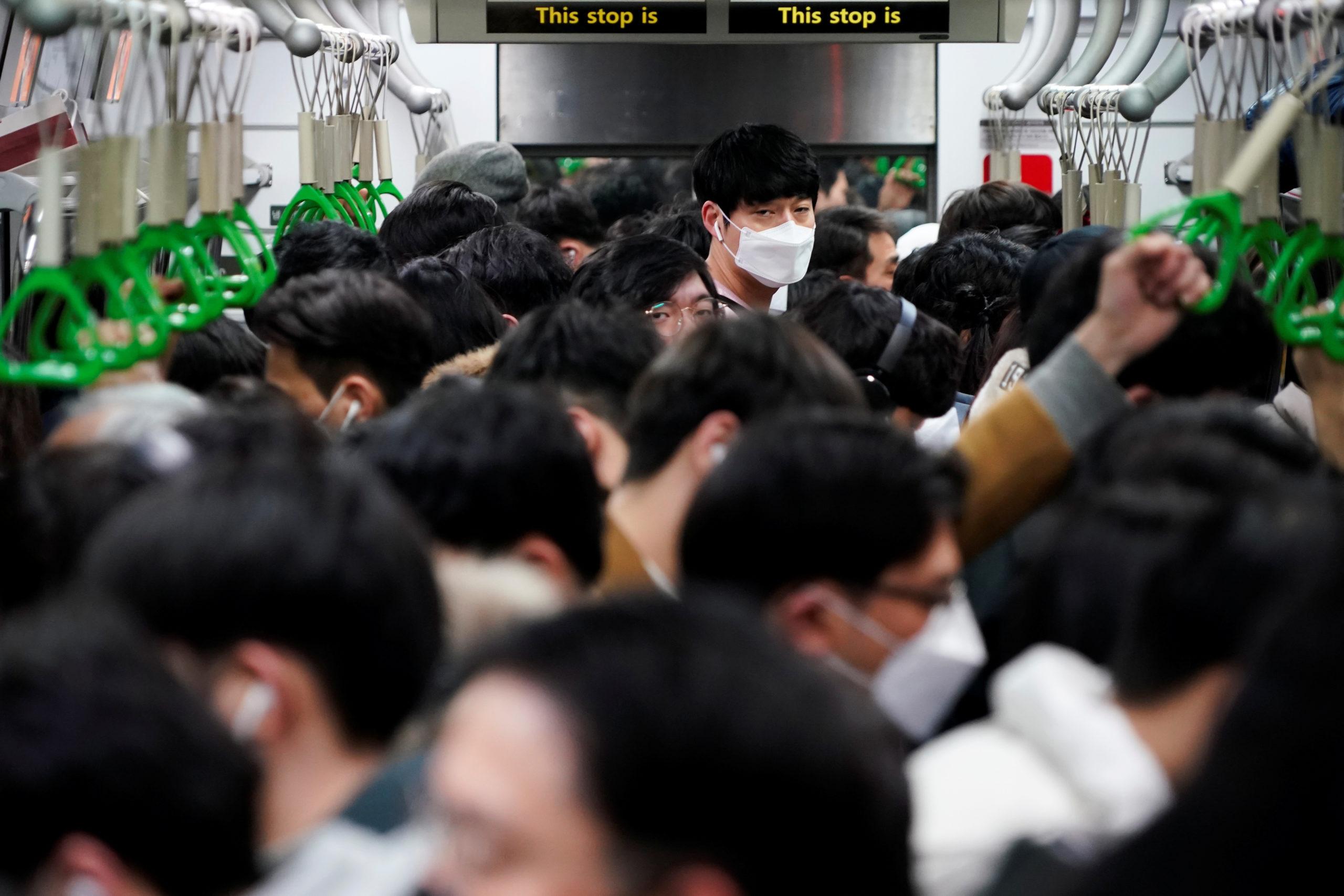 Un treno a Seul pieno di pendolari con mascherine protettive
