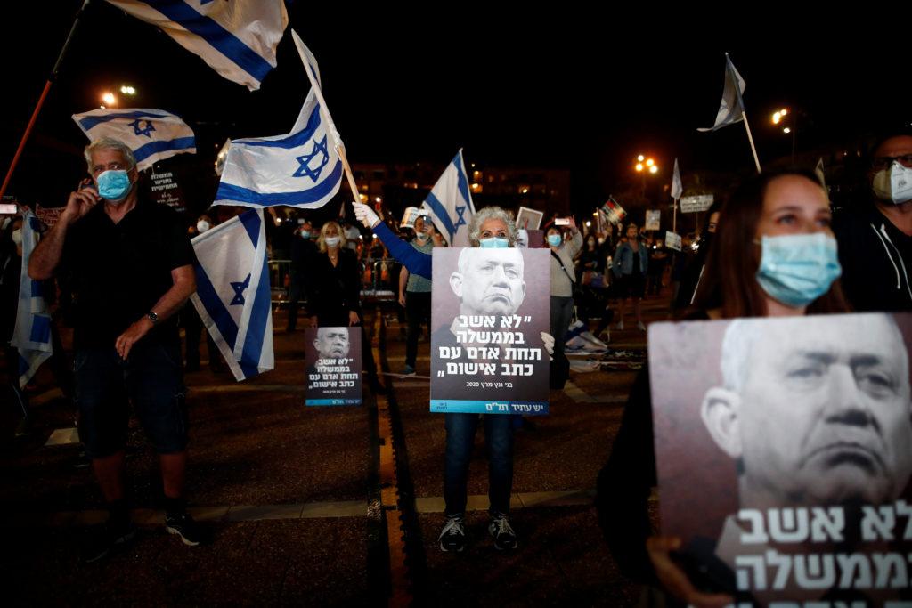 """Israele, Netanyahu-Gantz: parte il Governo di emergenza. Gli israeliani mostrano manifesti con l'immagine di Benny Gantz, capo del partito Blu e Bianco, che dicono: """"Non starei in un Governo con un uomo con accuse criminali"""", mentre protestano contro il Primo Ministro israeliano Benjamin Netanyahu in piazza Rabin a Tel Aviv, Israele, 19 aprile 2020. REUTERS/Corinna Kern"""