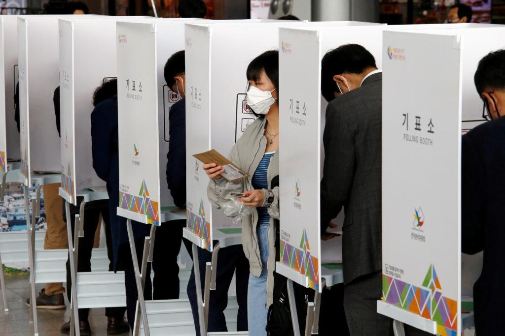 Corea del Sud: il coronavirus non ferma le elezioni. Una donna che indossa una maschera per evitare di contrarre il coronavirus lascia una cabina elettorale per esprimere il proprio voto alle elezioni parlamentari in un seggio elettorale a Seul, Corea del Sud, 10 aprile 2020. REUTERS/Heo Ran