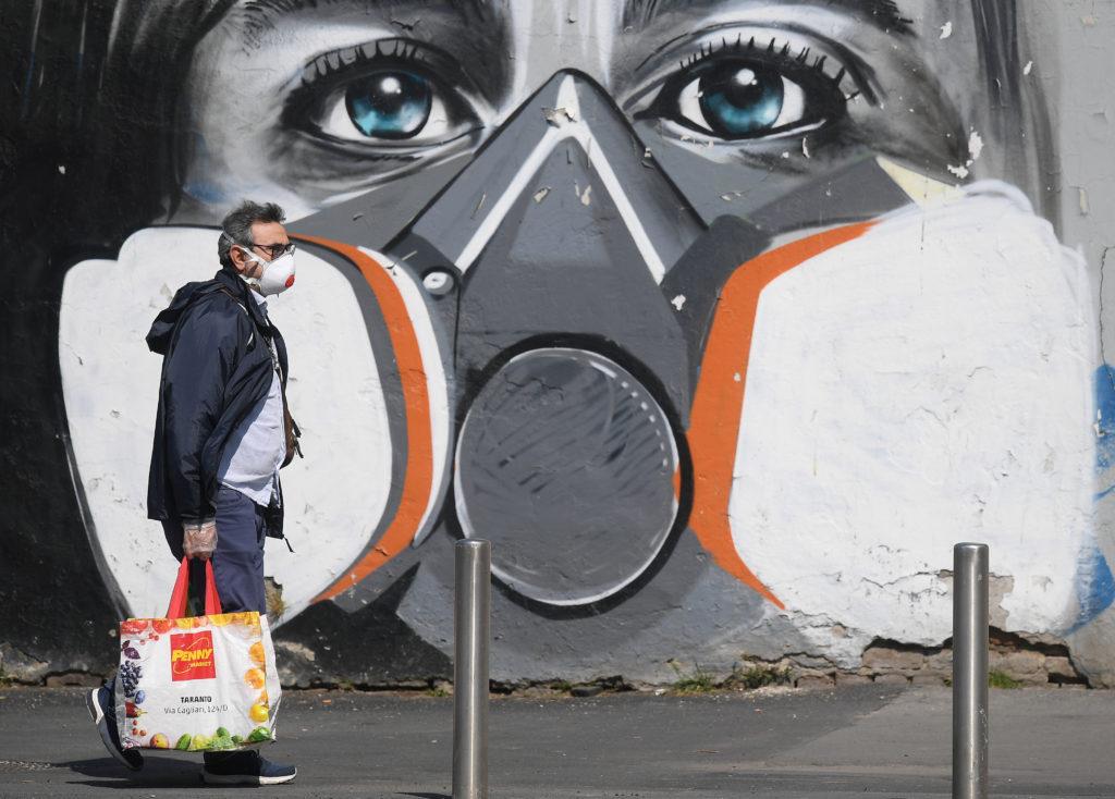 Coronavirus, Italia: i contagi calano, si prepara la fase 2. Un uomo che indossa una mascherina protettiva passa davanti a un graffito a Milano, 6 aprile 2020. REUTERS/Daniele Mascolo