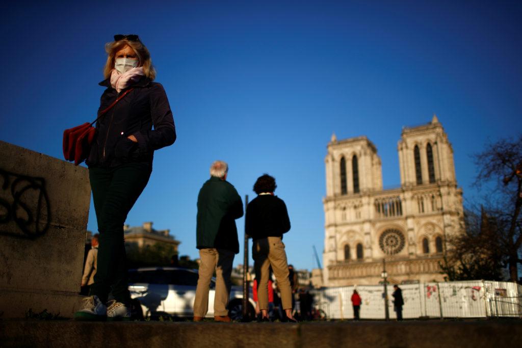 Coronavirus, Apple: scontro sulla privacy con Parigi. La gente ascolta il suono della grande campana della cattedrale di Notre-Dame de Paris, come segno della resilienza dell'edificio un anno dopo un devastante incendio, durante l'epidemia di coronavirus, Francia, 15 aprile 2020. REUTERS/Gonzalo Fuentes