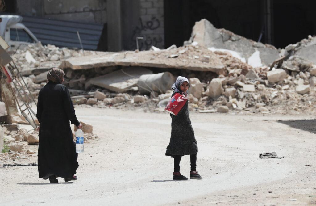 Siria, l'inviato speciale Geir Pedersen annuncia: presto meeting con le parti. Una ragazza cammina vicino alle macerie di edifici danneggiati nella città di Nairab, nella regione ribelle di Idlib, Siria, 17 aprile 2020. REUTERS/Khalil Ashawi