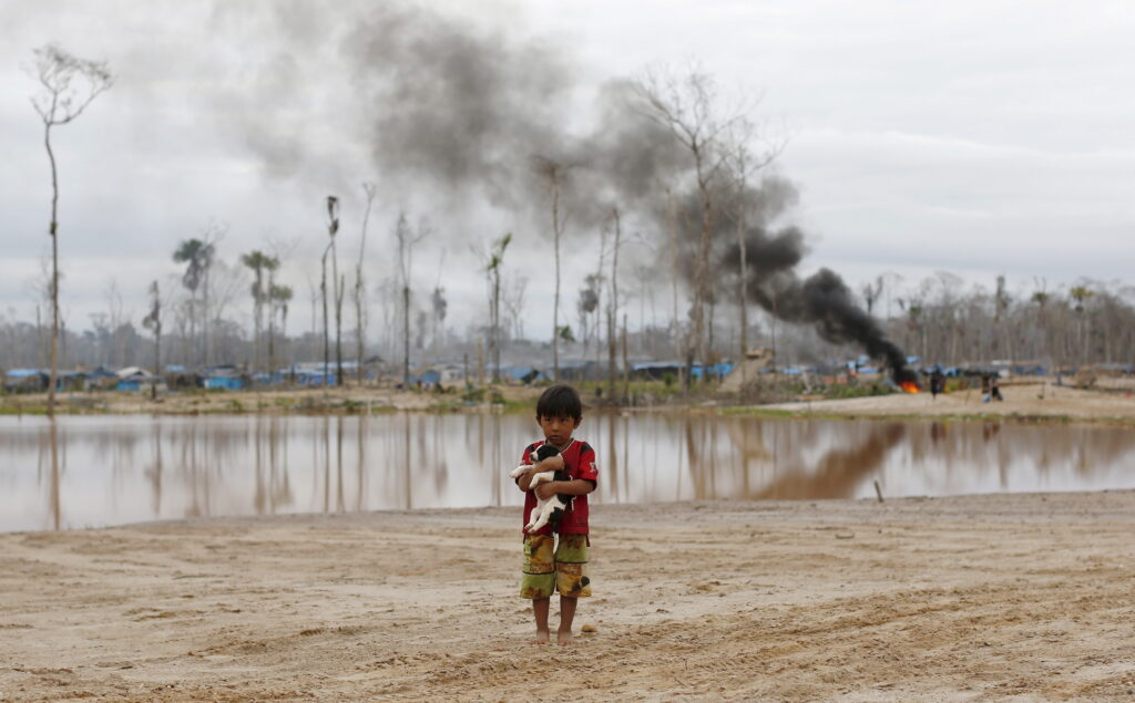 Perù: il traffico illegale dell'oro.Un bambino porta in braccio un cane mentre si allontana da un'operazione della polizia peruviana per distruggere campi illegali di miniere d'oro in una zona conosciuta come Mega 14, nella regione amazzonica meridionale di Madre de Dios, Perù. REUTERS/Janine Costa